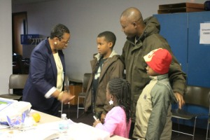 An election judge explains the voting process to Schaumburg dad George Matthew's children.